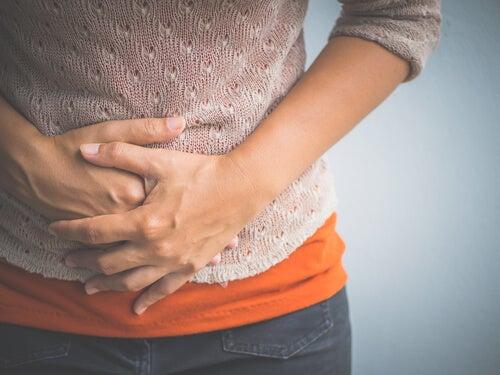 Mujer con manos en la barriga por dolor menstrual