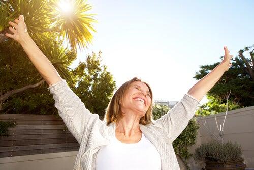 Mujer mayor feliz abriendo los brazos