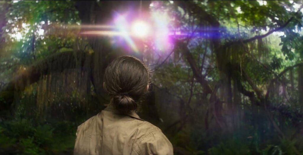 Mujer mirando una luz entre árboles