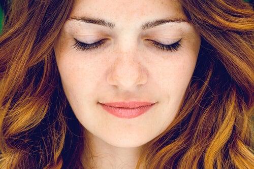 Mujer sonriendo con los ojos cerrados pensando en las consecuencias negativas de la automatización