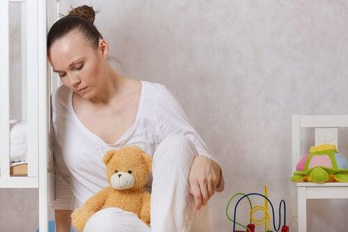 Mujer triste apoyada en una cuna