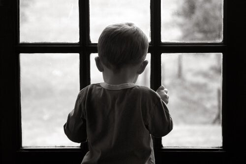 Niño triste y solo mirando por la ventana simbolizando la depresión infantil