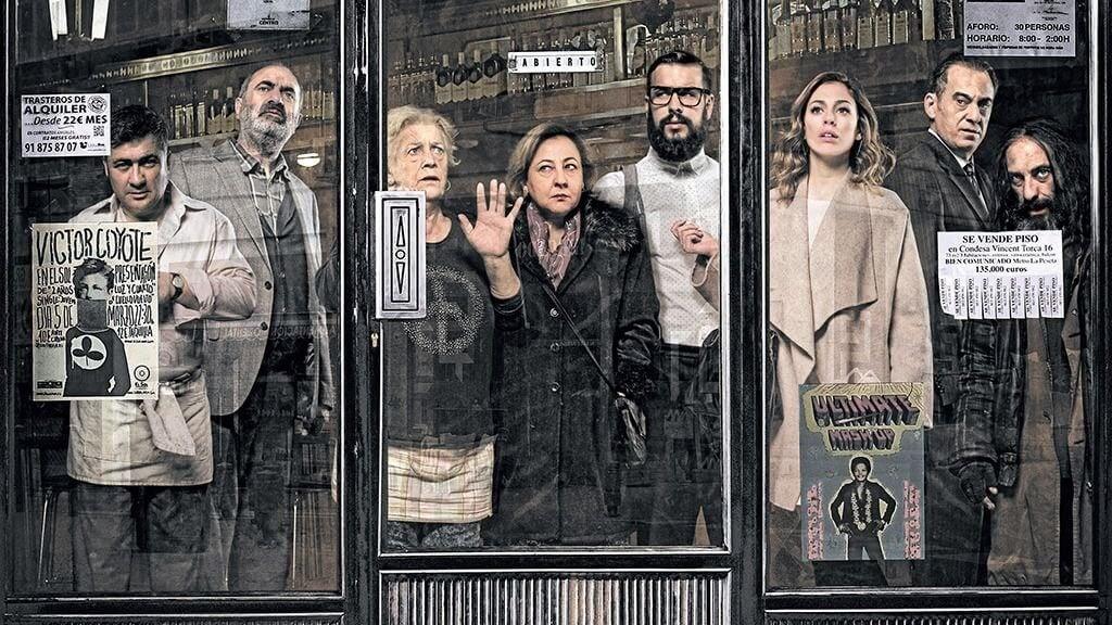 Personas asomadas tras los cristales de un bar