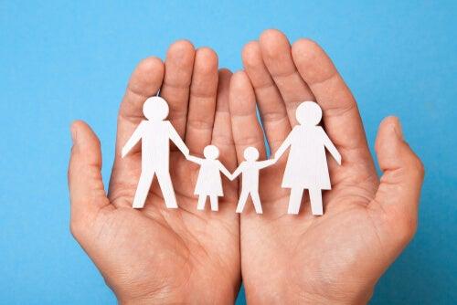 Mano sujetando unas figuras con forma de familia