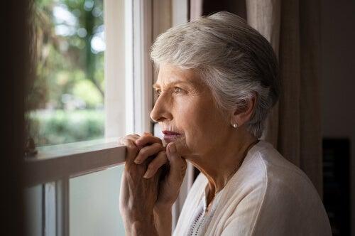Mujer con demencia mirando por la ventana