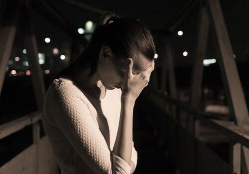 Mujer triste en un puente sintiendo la culpa