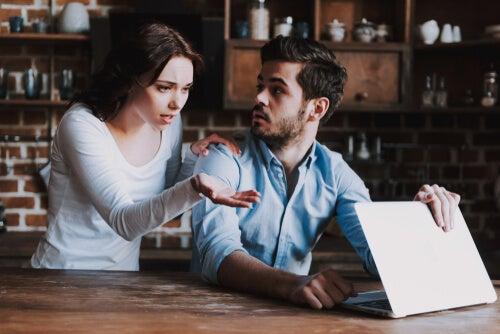 Chica mirando a su novio cuando está con el ordenador sospechando una infidelidad online