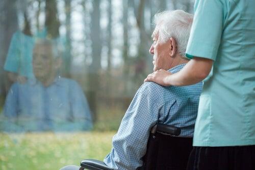 Hombre mayor con una auxiliar mirando por la ventana