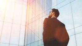 Hombre mirando un rascacielos mientras piensa en reinventarse