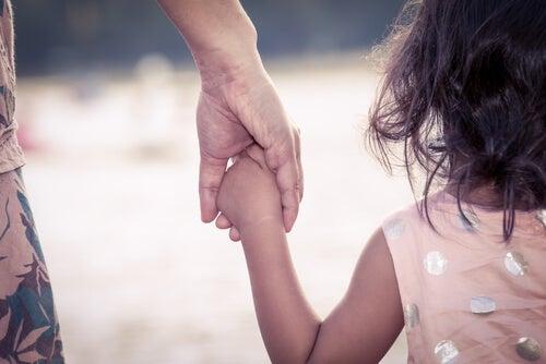 Madre agarrando a su hija de la mano