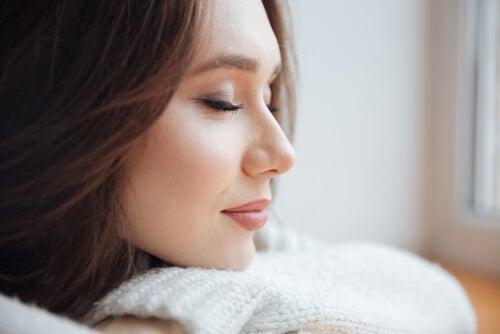 Mujer con los ojos cerrados experimentando ASMR