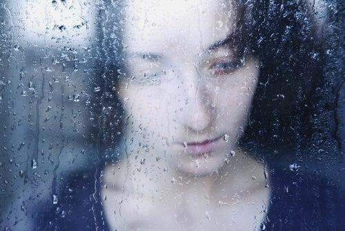 Mujer triste tras una ventana pensando en los vacíos emocionales