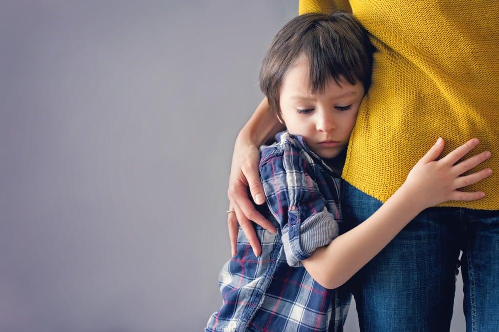 Niño con miedo abrazando a su madre