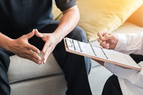 Psicólogo completando un informe mientras observa al paciente
