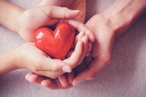 Manos sujetando un corazón para representar la importancia de los cuidados