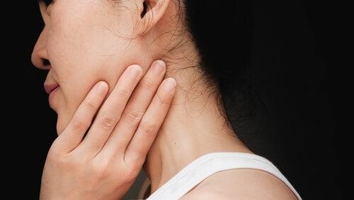 Mujer con una mano en el cuello