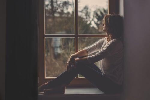 Mujer en una ventana pensando en cuando todo nos da igual