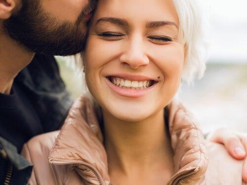Hombre dando a un beso a su mujer sonriendo