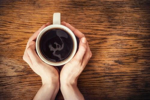 Manos de una mujer con una taza de café