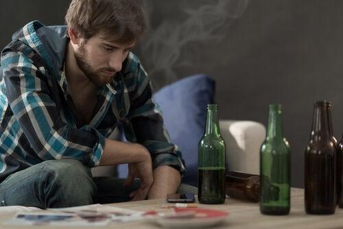 Chico joven con botellas de alcohol en la mesa