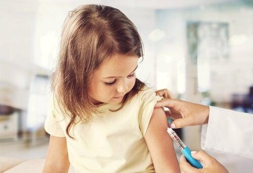 Enfermera poniendo una vacuna a una niña
