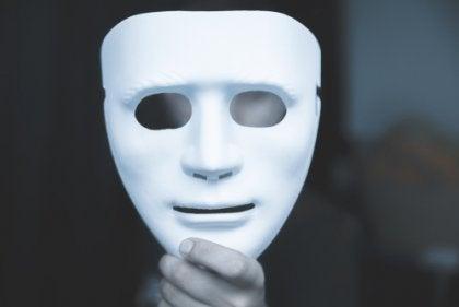 Hombre sujetando una máscara para representar a las personas cínicas