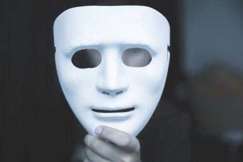 Hombre sujetando una máscara para representar las mentiras blancas