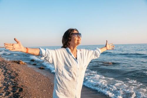Mujer mayor con los brazos abiertos en la playa