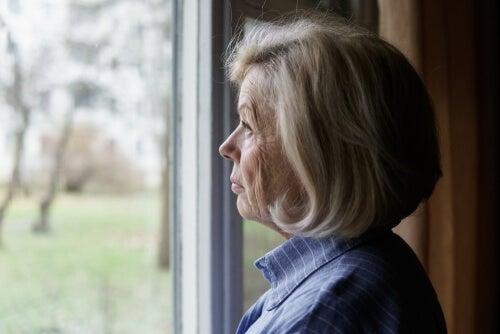 Mujer mayor mirando una ventana