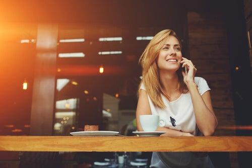 Mujer sonriendo mientras toma un café