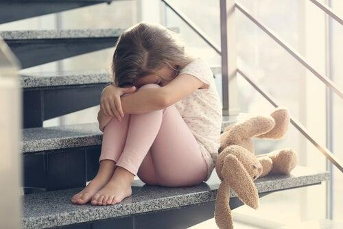 Niña con ansiedad sentada en la escalera