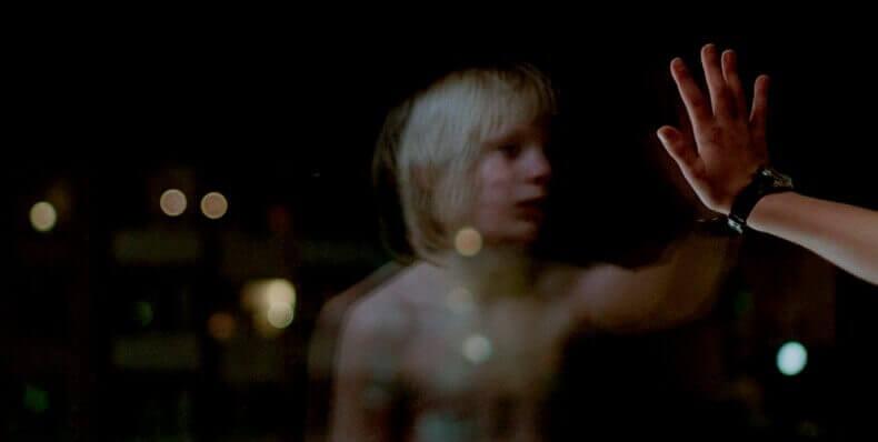 Niño poniendo mano sobre un cristal