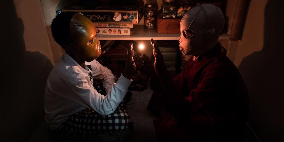 Niños con máscaras sentados enfrente uno del otro, escena de Nosotros