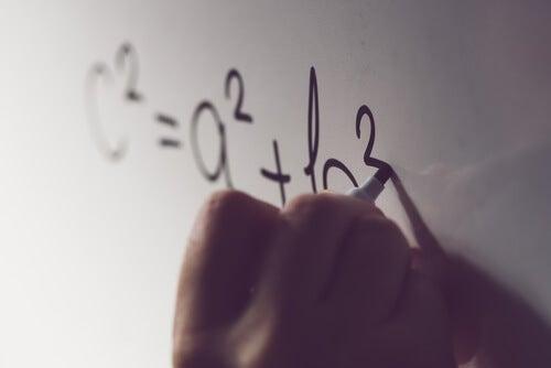 Persona escribiendo el teorema de Pitágoras en la pizarra