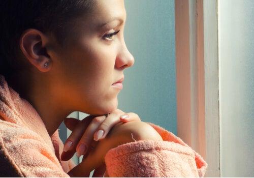 Mujer con cáncer mirando por la ventana