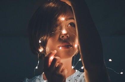 Mujer con luces representando la felicidad sintética