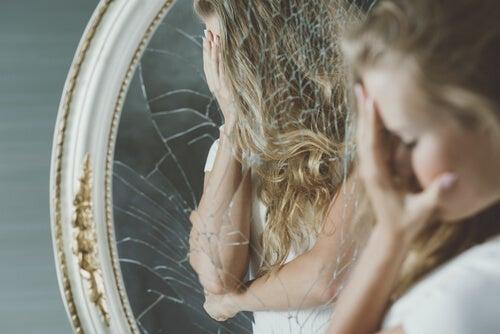 Mujer triste mirándose al espejo