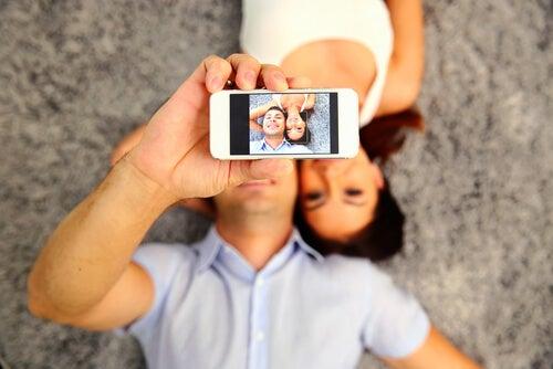 Pareja haciéndose un selfie representando las diferencias entre hombre mujer