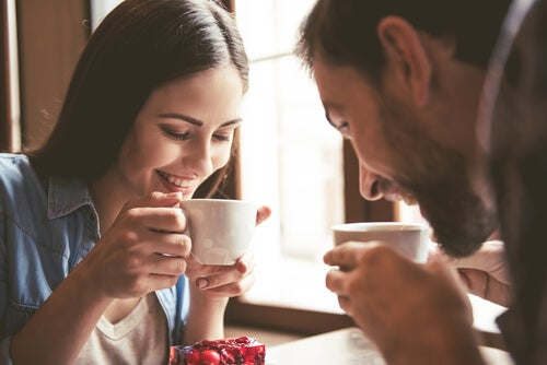 Pareja sonriendo tomando un café