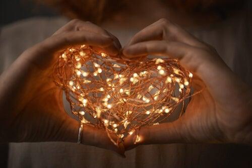 manos con corazón de luces simbolizando la admiración en la pareja