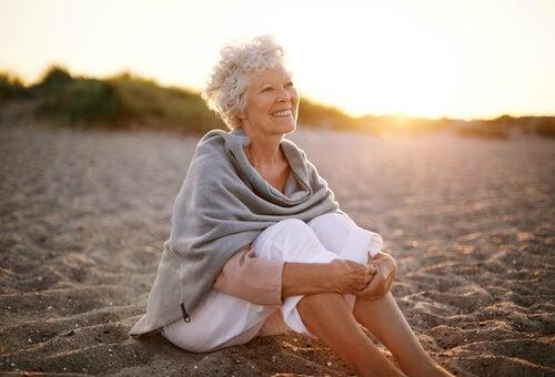 Mujer jubilada sentada en la playa
