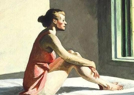 Mujer sentada mirando por la ventana