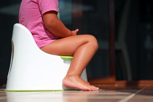 Niña sentada en un WC