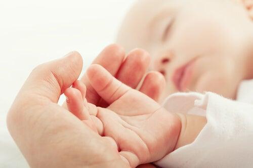 Padre acariciando la mano de su bebé