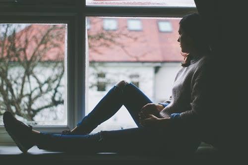 Chica ante mirando el exterior simbolizando lo que vemos desde la ventana