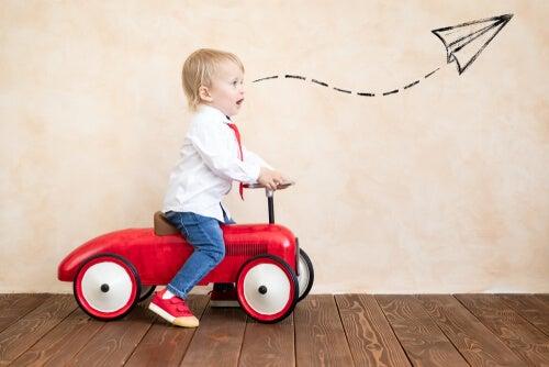 Niño jugando con un coche rojo