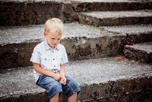 Niño llorando sentado en una escalera