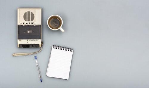 Grabadora con un café y una libreta