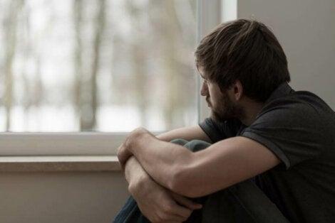 Chico con fobia social en casa mirando por la ventana