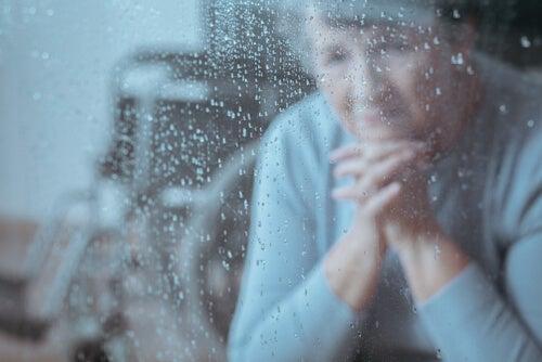 Mujer mayor mirando la lluvia por la ventana